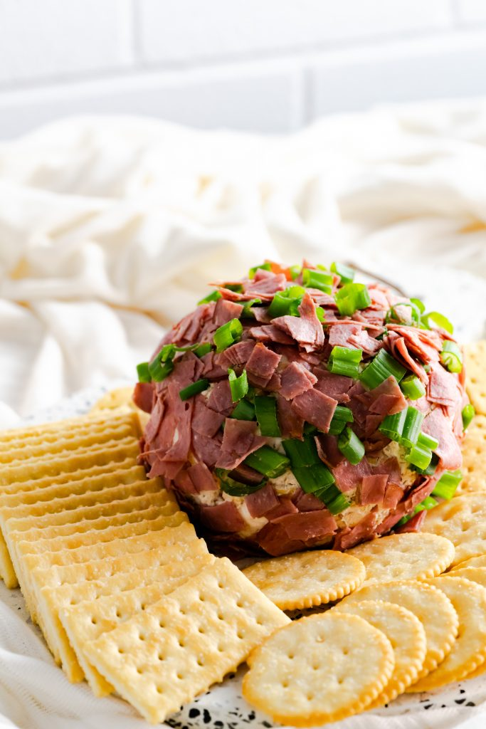 Dried Beef Cheese ball on a platter surrounded by crackers.
