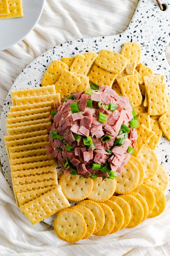 Cheese ball covered in chipped beef and scallions surrounded by a variety of crackers.