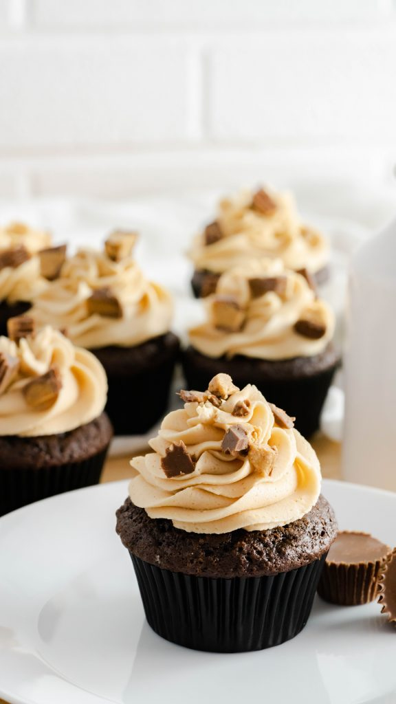 Chocolate cupcakes with peanut butter buttercream frosting on a white plate.
