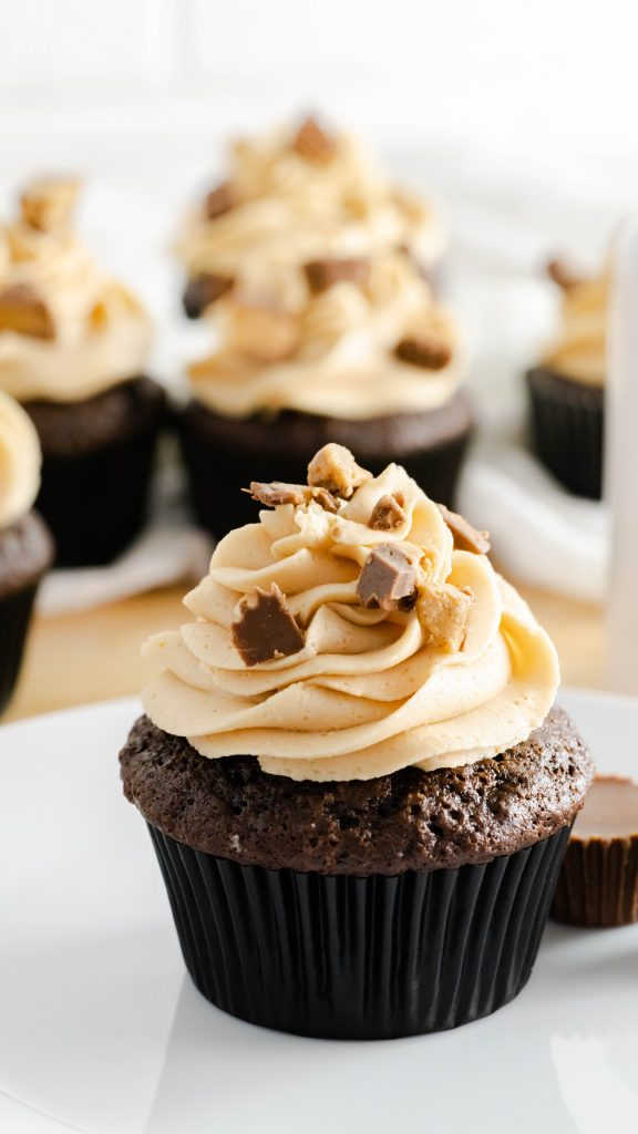 Chocolate cupcake in black wrapper with peanut butter frosting topped with chopped peanut butter cups.