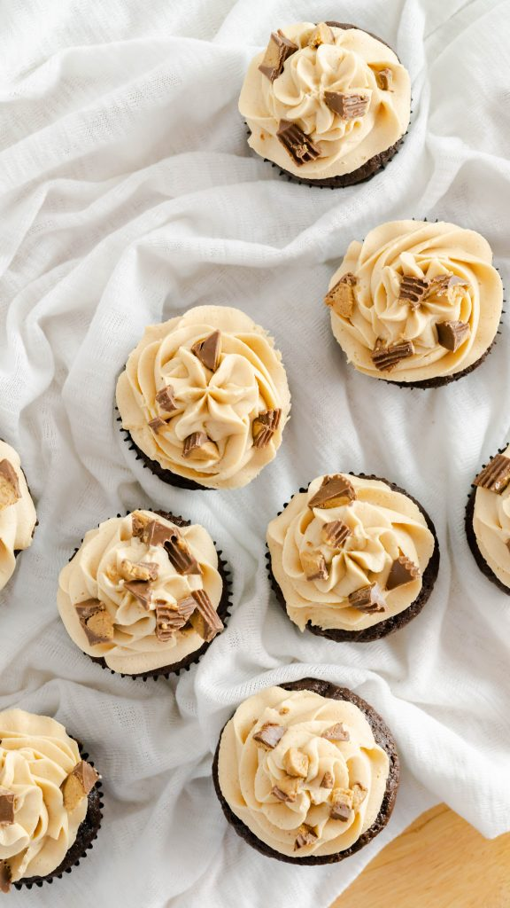 Top view of chocolate cupcakes with peanut butter frosting and chopped peanut butter cups.