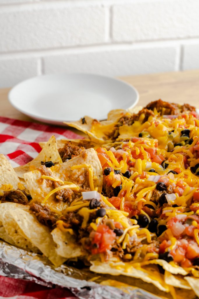 Sheet pan with pulled pork nachos that are tolled with salsa, black beans, and cheese.