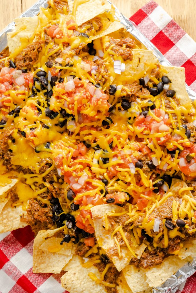 Loaded pulled pork nachos with pulled pork, salsa, beans, and cheese sitting on red checkered napkin.