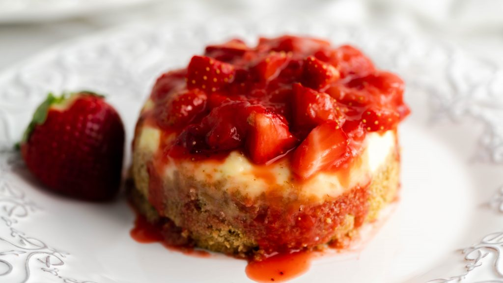 Decorative plate with a cheesecake sitting on it topped with strawberries.