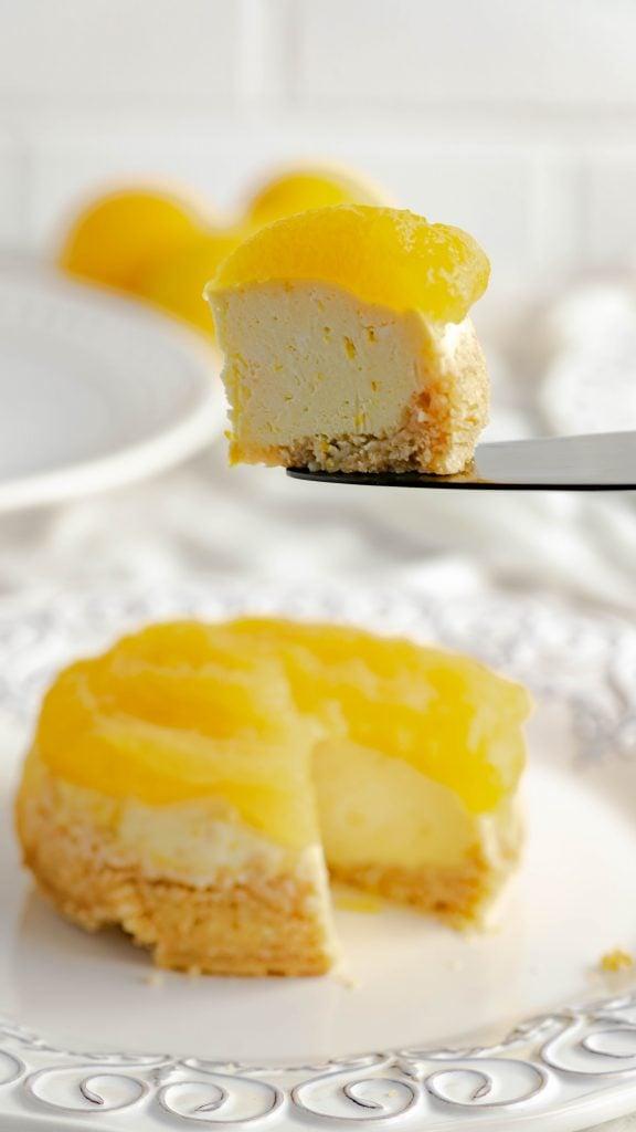 Lemon cheesecake with lemon curd on top sitting on a black serving utensil.