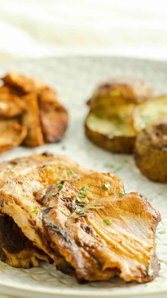 Sliced bourbon pork tenderloin on a plate with sides of potatoes.