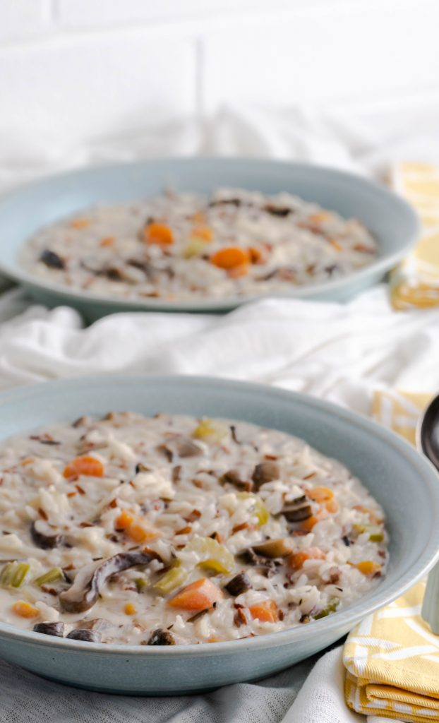 Wild rice and mushroom soup in a blue bowl with a yellow napkin.