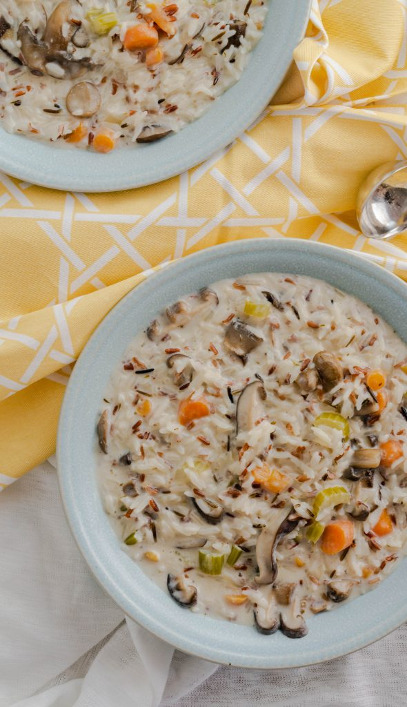Two bowls of wild rice and mushroom soup with yellow napkins.