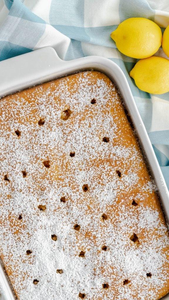 Lemon poke cake in white baking dish dusted with powdered sugar.