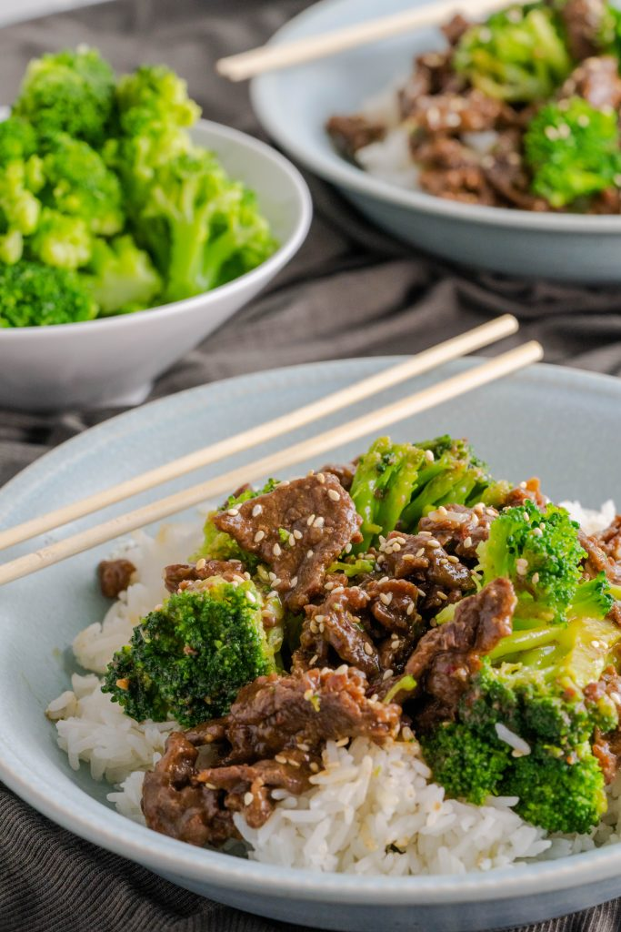 A bowl of jasmine rice topped with sesame beef and sesame seeds and broccoli.