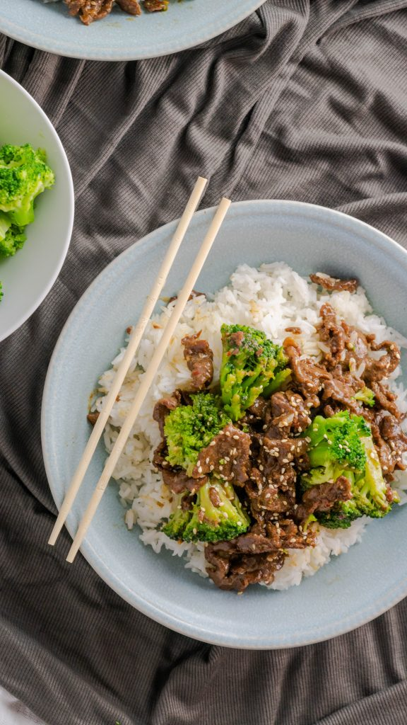 Chopsticks propped on bowl of beef broccoli and rice.