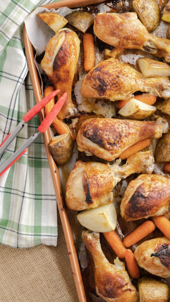 Sheet pan with chicken drumsticks, quartered potatoes, and baby carrots.