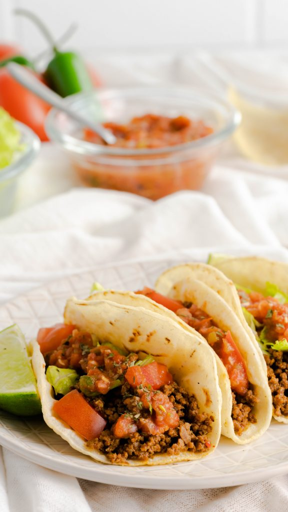 Three restaurant-style ground beef tacos on a decorative plate with red salsa in the background.
