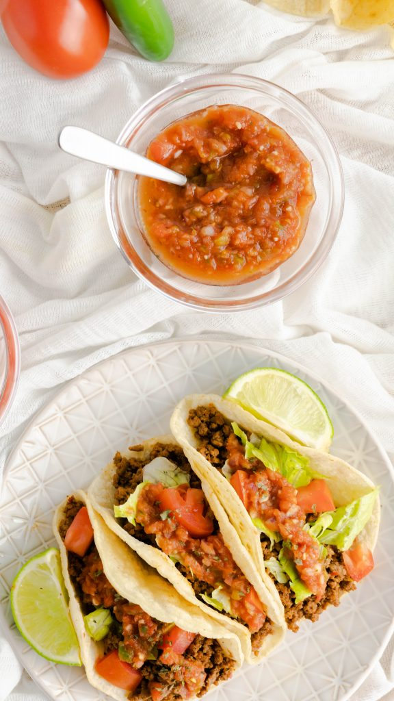 Restaurant-style ground beef tacos on corn tortillas and fresh ingredients.