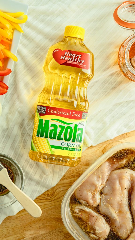 Raw chicken in marinate next to container of Mazola Corn Oil.