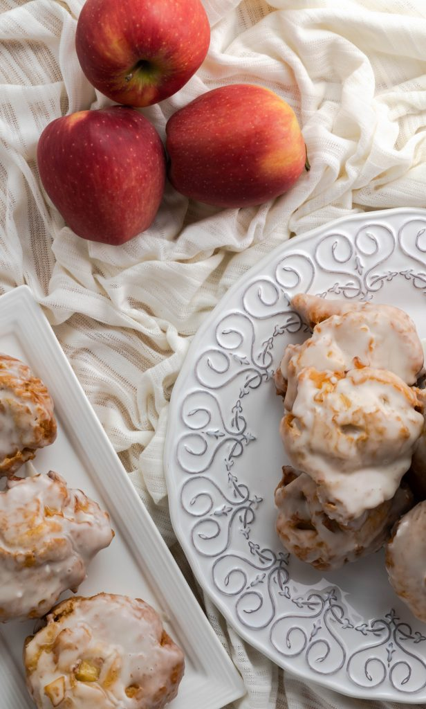 Three apple fritters on rectangular plate and stacked fritters on decorative round plate.