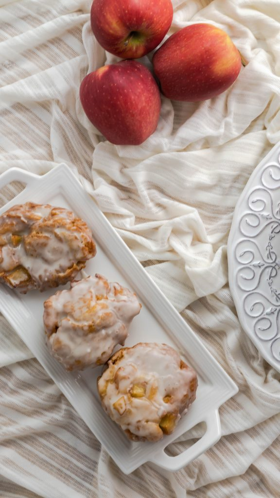 Glazed apple fritters on a rectangular plate with three apples next to it.