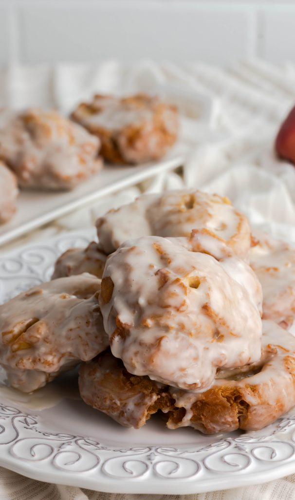 Stacked glazed homemade apple fritters on a decorative plate.