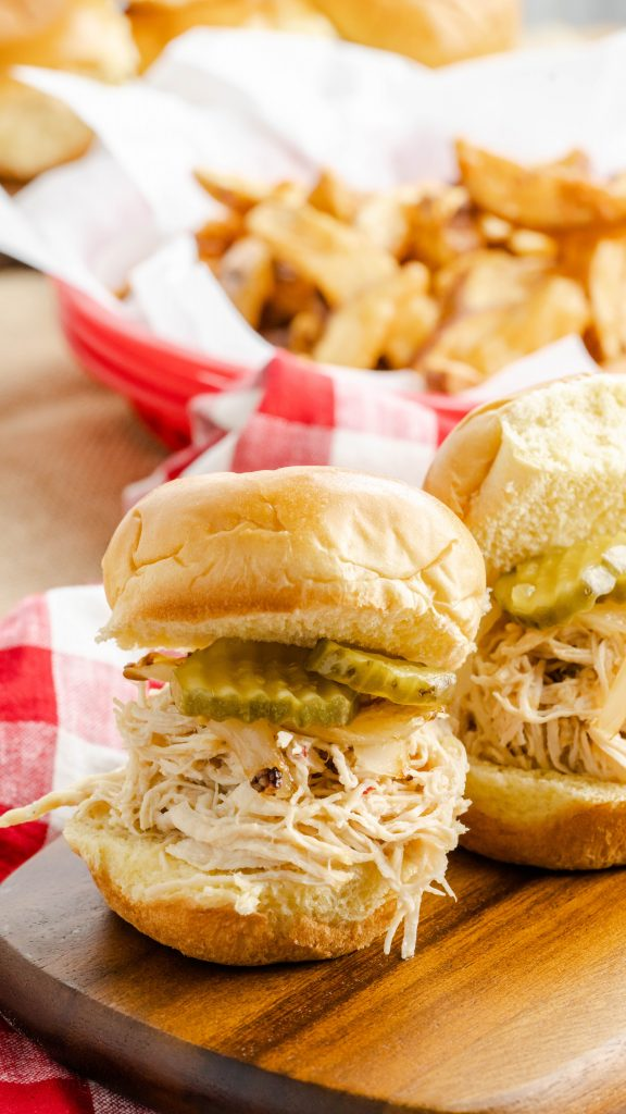 Pulled chicken topped with sliced pickles on slider buns.