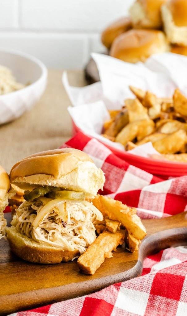 Serving paddle with pulled chicken slider with pickles and oven fries.