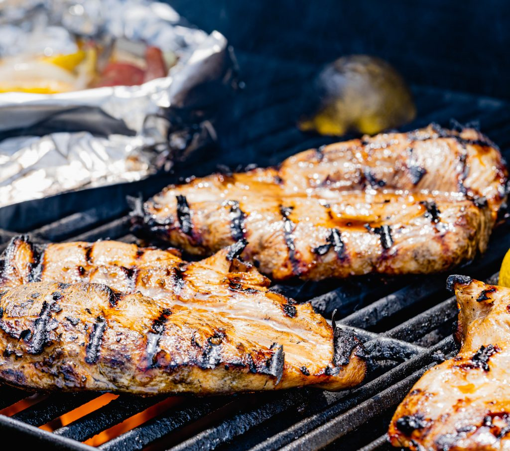 Chicken breasts with grill marks on grill grate with cut lemons.