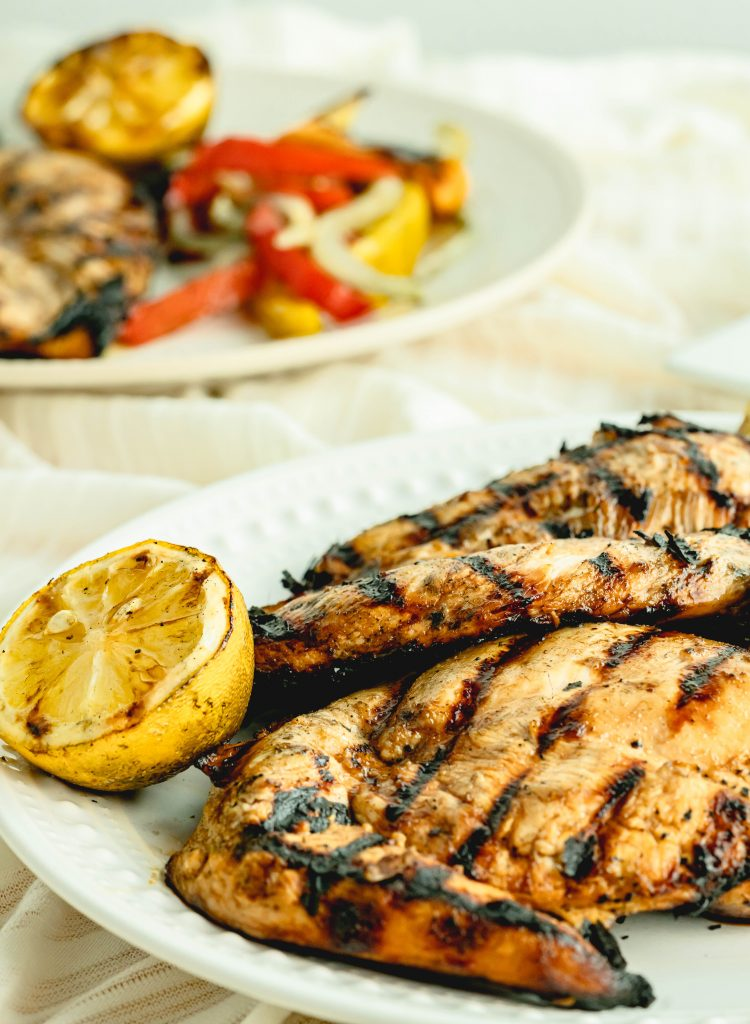 Close up of platter with grilled chicken and a cut lemon.