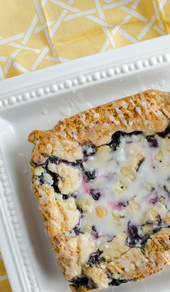 Glazed blueberry lemon bars uncut on white square dish.