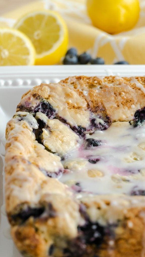 Uncut blueberry lemon bars on square serving platter.