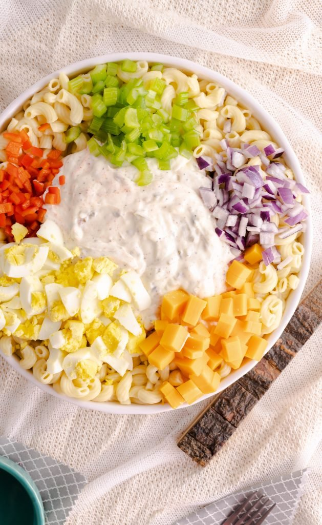 Instant Pot Macaroni Salad ingredients consisting of eggs, cheese, red pepper, pasta, red onion, and celery.