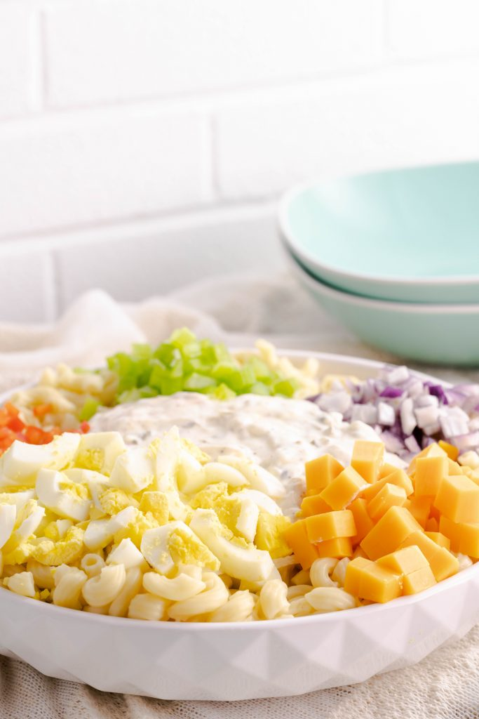 Side view of macaroni salad ingredients with dressing.