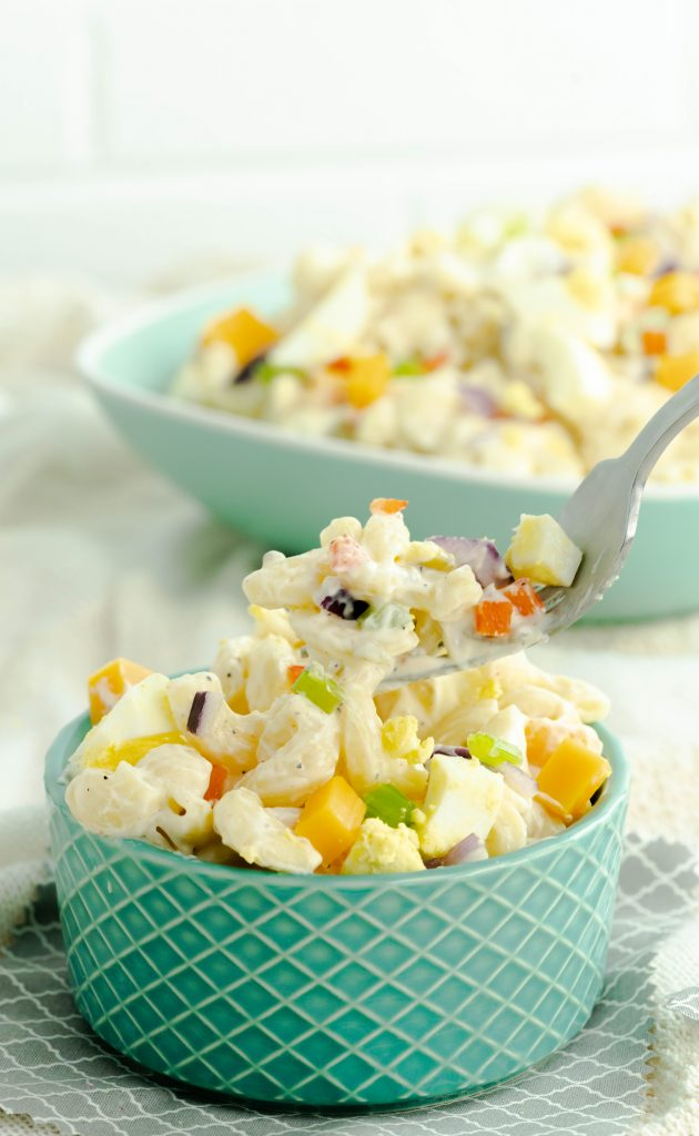 A forkful of macaroni salad with red onion, cheddar cheese, and celery pieces.
