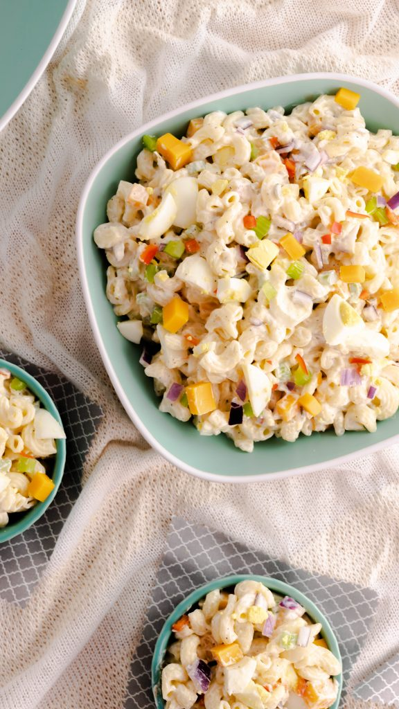 Top view of macaroni salad in one large bowl and two small bowls sitting on white fabric.