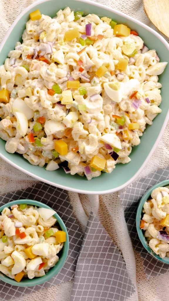 Macaroni Salad in a green serving bowl with two small bowls filled with macaroni salad.
