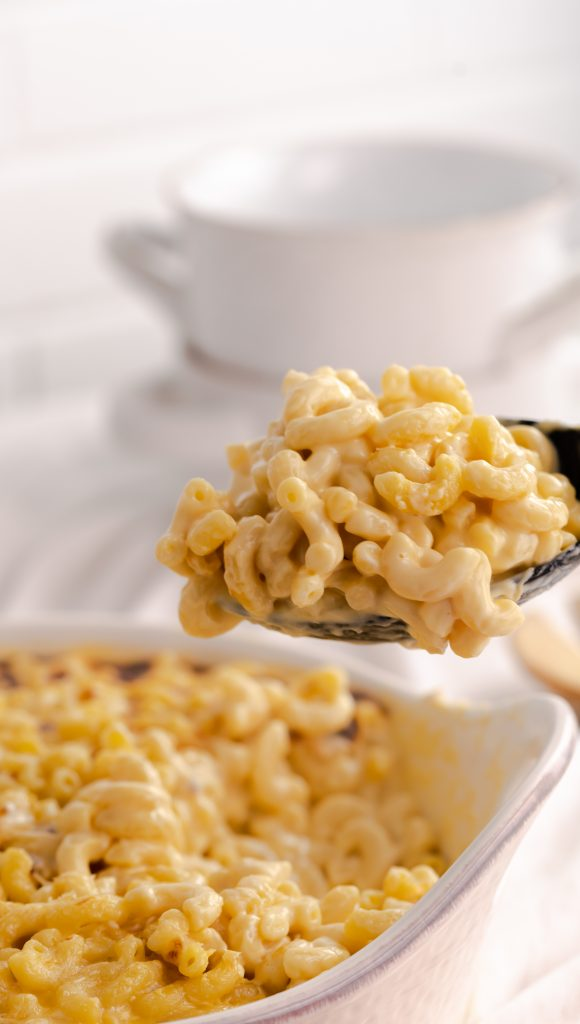 A closeup of a serving spoon full of mac and cheese.