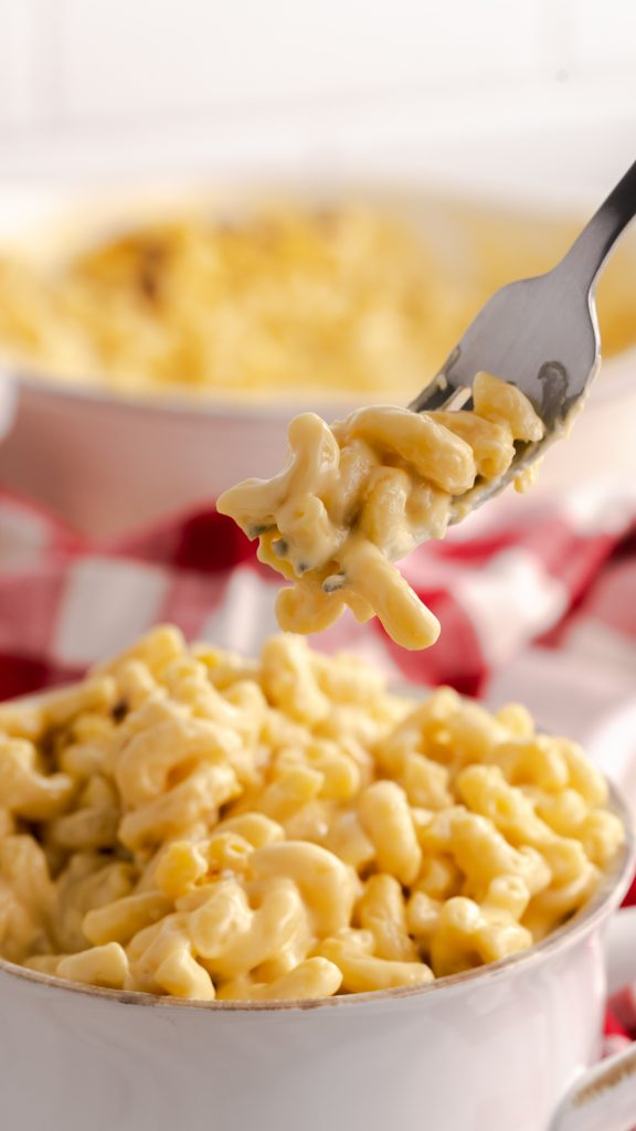 A fork of cheesy mac and cheese with a red and white napkin in background.