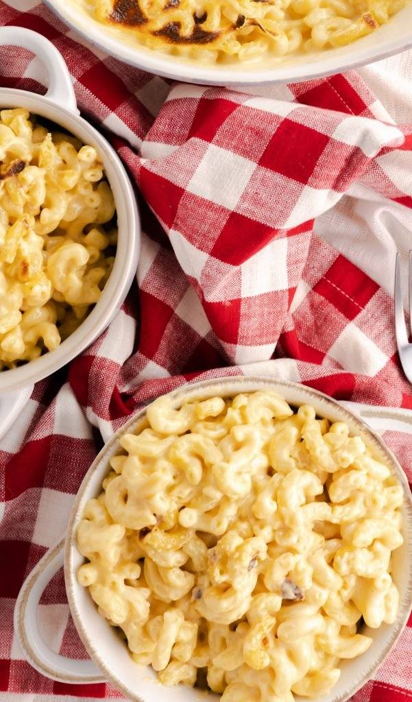 Top view of a bowl of mac and cheese in a white-rimmed bowl with handles.