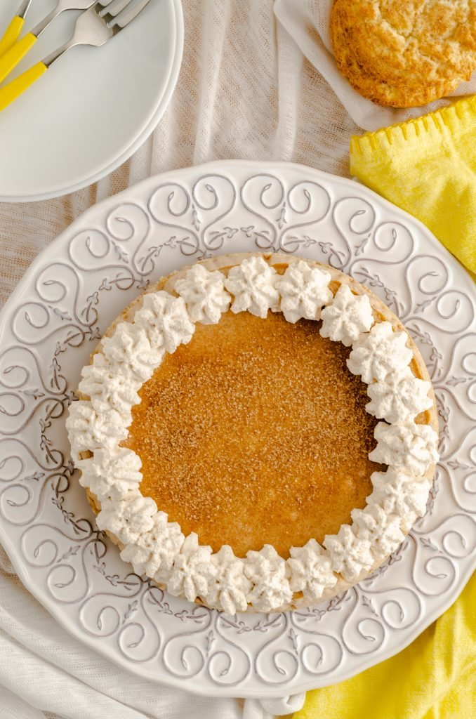 A 7 inch snickerdoodle cheesecake garnished with cinnamon and decorated with homemade whipped cream.