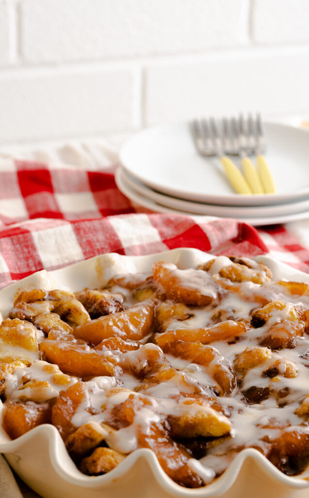 Apple cinnamon roll bake breakfast casserole with three plates and three yellow forks sitting behind it.