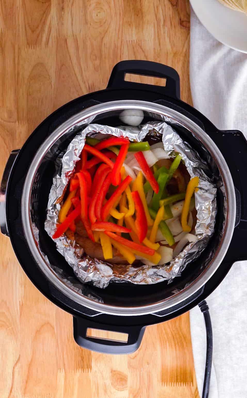 Top view of pressure cooker with chicken fajita ingredients in aluminum foil.