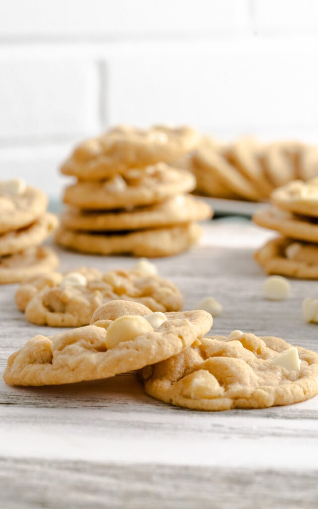 Two macadamia nut cookies with white chocolate chips on gray background.
