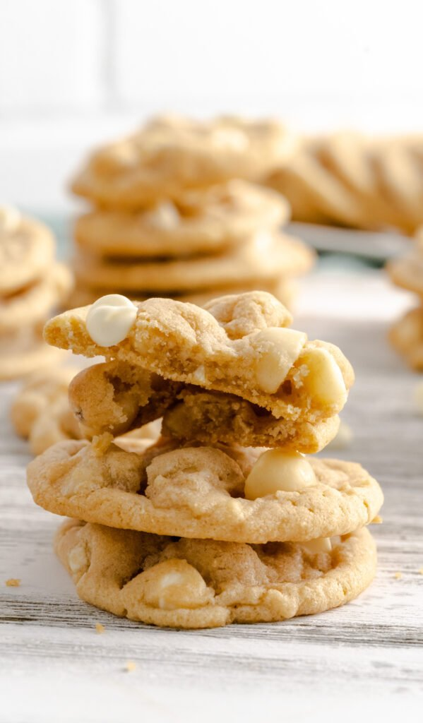 A stack of white chocolate macadamia nut cookies with cookies stacked behind it.