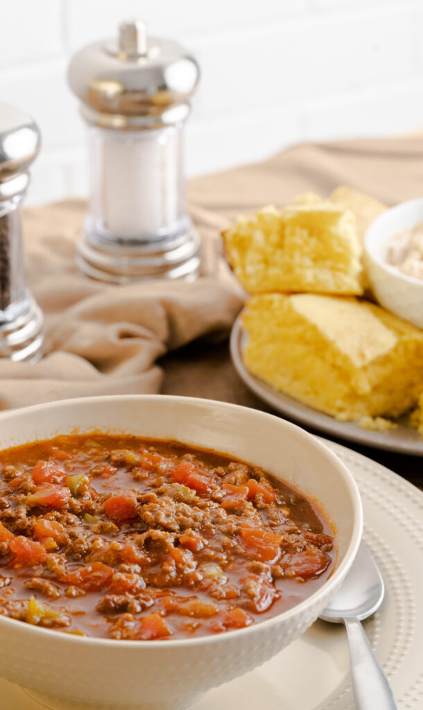 Bowl of no bean chili served in a beige bowl with a side of cornbread.