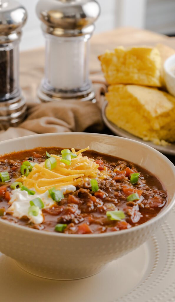 Bowl of keto Instant Pot no-bean chili garnished with sour cream and shredded cheese.