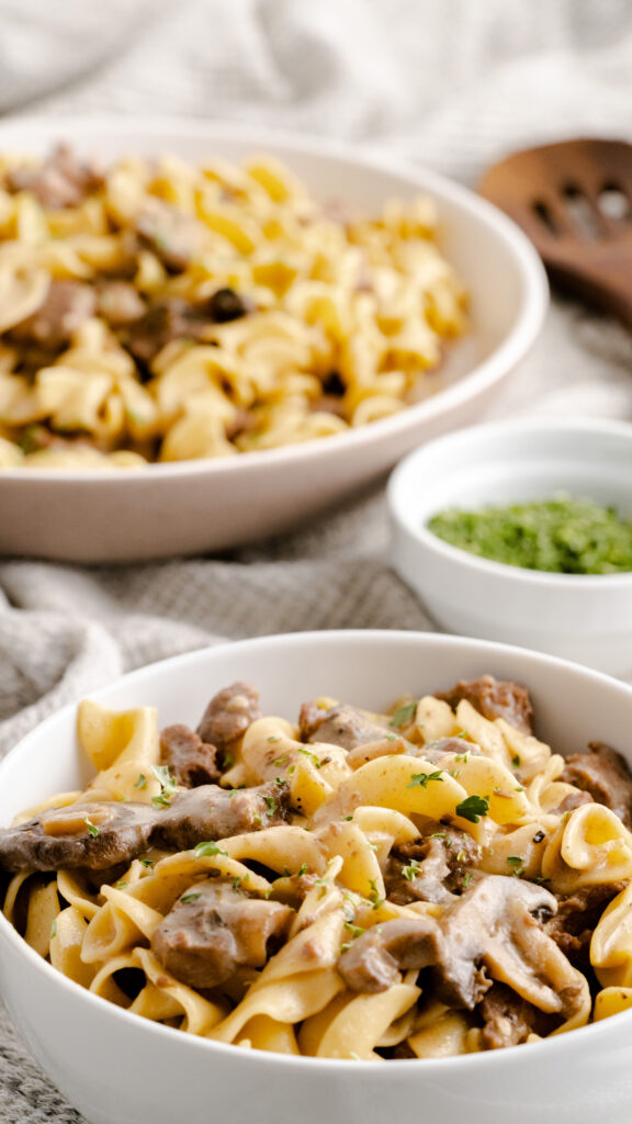 Instant Pot homemade beef stroganoff served in a white bowl with parsley on the side.