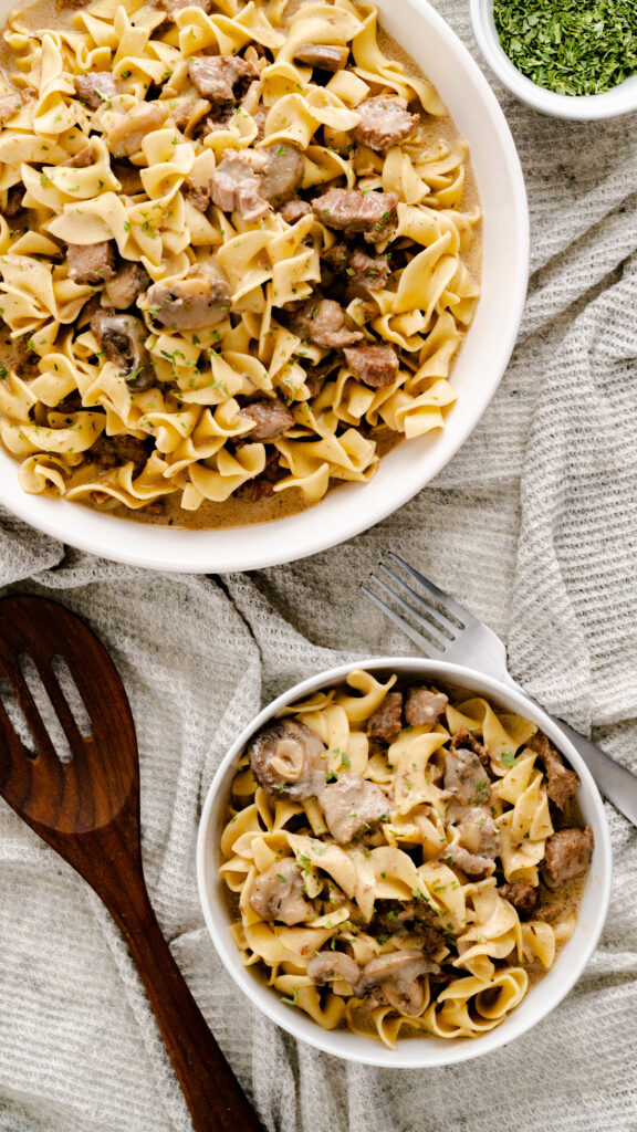 A bowl of beef stroganoff with a serving bowl of Instant Pot Beef Stroganoff beside it.