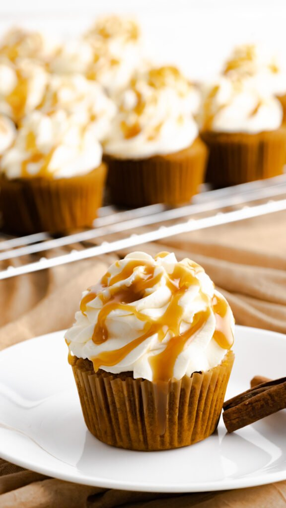 Cupcake with caramel drizzle sitting on a white plate with a background of pumpkin spice cupcakes on wire rack.