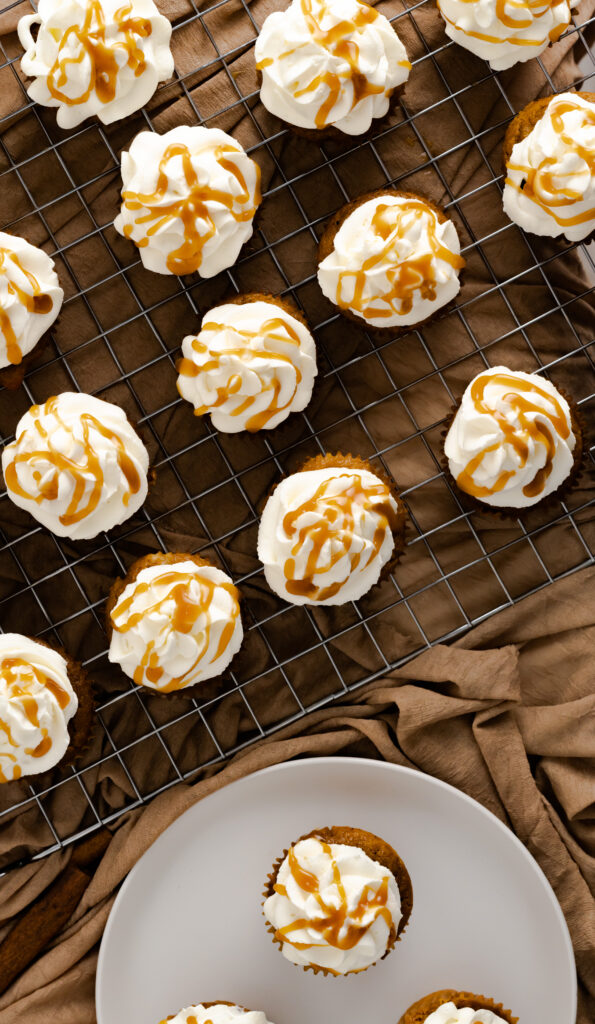 Pumpkin spice cupcakes sitting on a cooling rack with a brown fabric background.