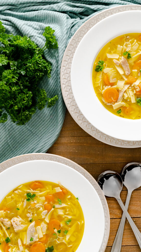 Two rimmed bowls of Instant Pot chicken noodle soup on a wooden serving board.