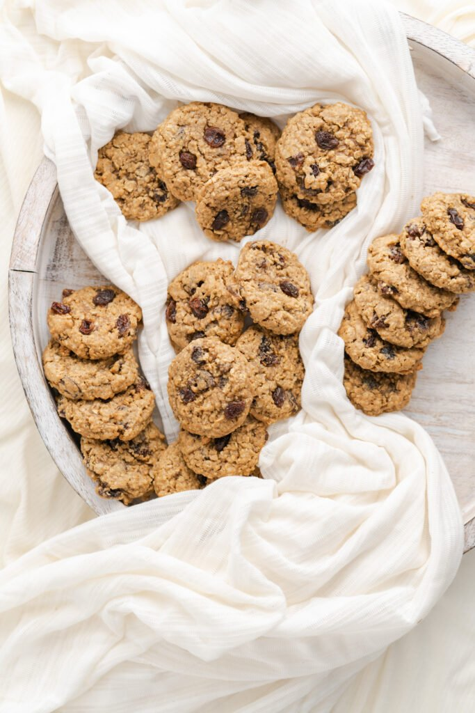 Oatmeal cookies with raisins on a wooden platter.