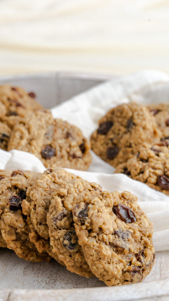 A wooden platter of oatmeal raisin cookies with white fabric.